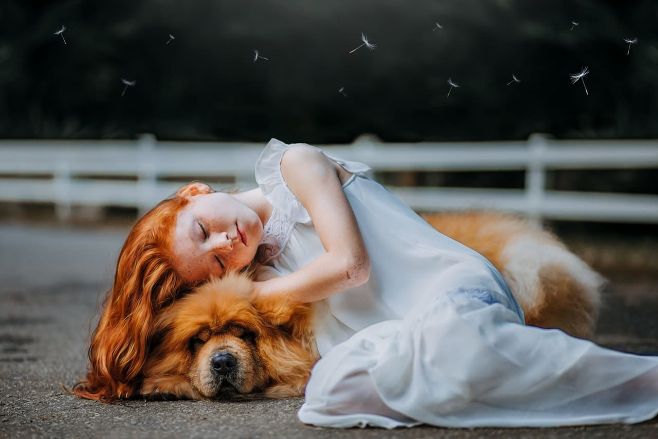 a photo of a red-haired girl resting her head on a dog